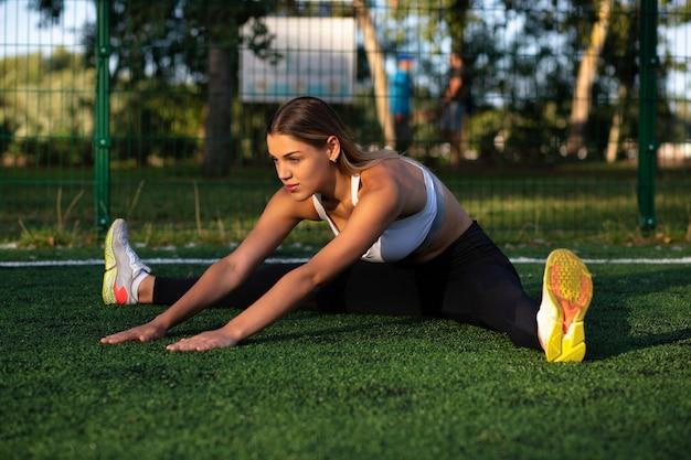 柔軟なフィットネスの女性は、トレーニングの前にウォームアップします