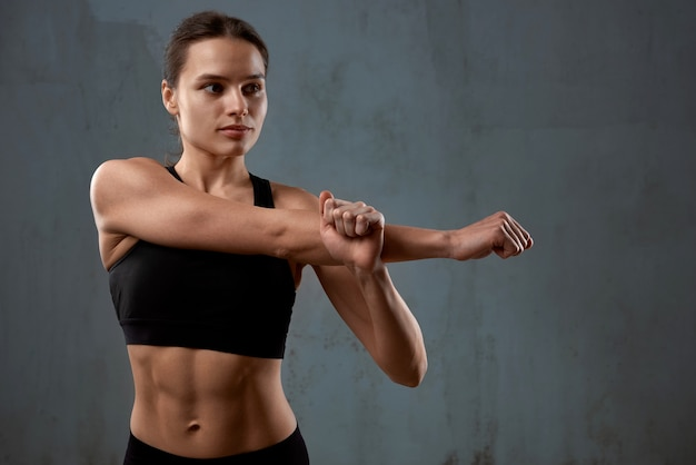 Flexible fitnesswoman stretching arm before training