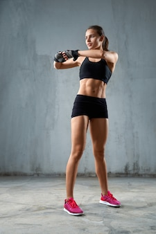 Flexible fitnesswoman stretching arms before training