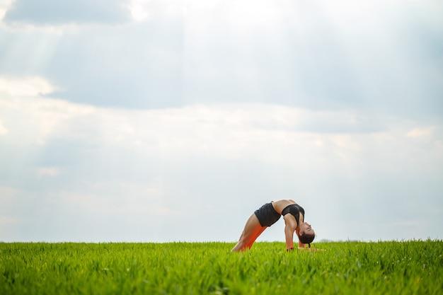 Гибкая девушка, акробат, гимнастический мост, стойка на руках, изящная женщина. на природе выполняет красивые позы для гибкости, спортивная модель на фоне голубого неба.