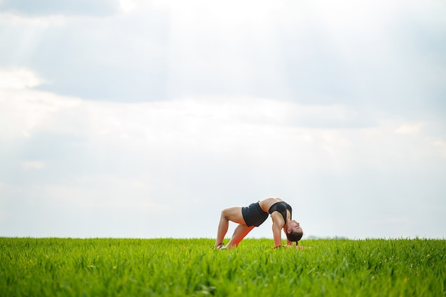 柔軟な女の子、アクロバット、体操の橋、逆立ち、優雅な女性。自然界では、青空を背景にしたスポーツモデルである柔軟性のために美しいポーズをとっています。