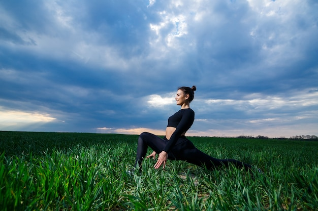 유연한 소녀, 곡예사, 체조 다리, 물구나무서기, 우아한 여성. 자연에서, 푸른 하늘 배경에 스포츠 모델, 유연성을 위해 아름다운 포즈를 수행합니다.