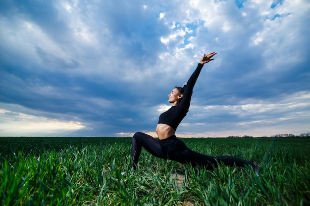Flexible girl, acrobat, gymnastic bridge, handstand, graceful woman. in nature, performs beautiful poses for flexibility, a sports model on a blue sky background.
