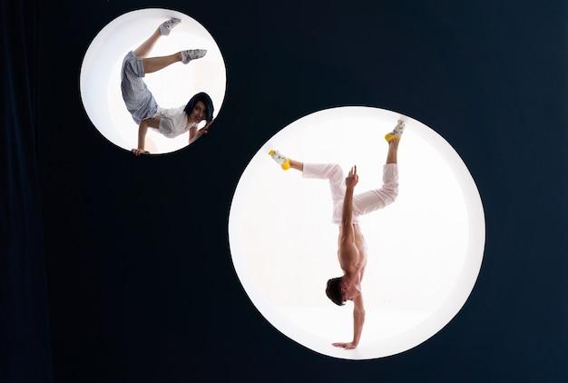 Гибкая девушка и мужчина делают растяжку и стойку на руках в студии концепции индивидуальности, творчества и самоуверенности