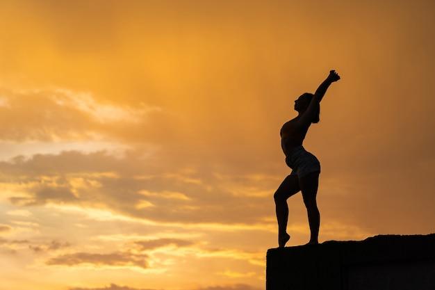 극적인 일몰 동안 하늘 배경에 운동을 하 고 유연한 소녀