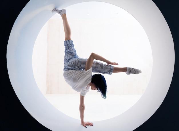 Гибкая девушка делает растяжку и стойку на руках в студии концепции здорового образа жизни и йоги