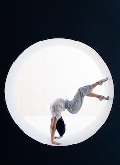 Flexible girl doing stretching and handstand in studio concept of healthy lifestyle and yoga