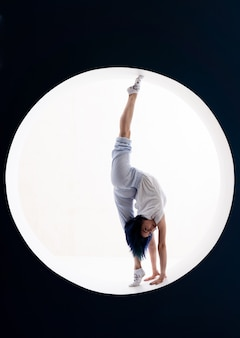 Flexible girl doing stretching and handstand in studio concept of individuality creativity concept