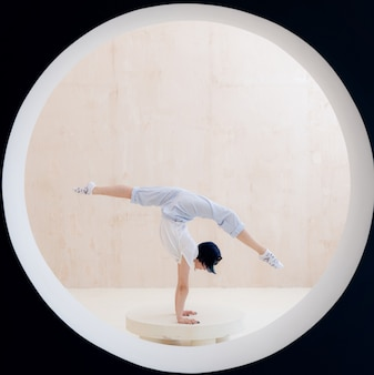 Flexible girl doing stretching and handstand in studio concept of individuality creativity and selfc...