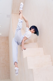 Flexible girl doing stretching and handstand in studio concept of individuality creativity and selfconfidence