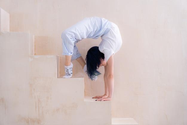 Гибкая девушка делает растяжку в студии концепции индивидуального творчества и йоги