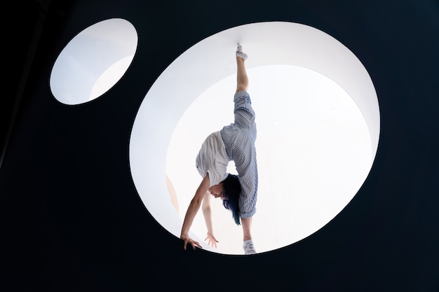 Flexible girl doing stretching in studio concept of individuality creativity and yoga