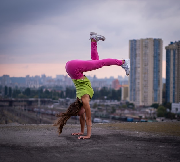 Flexible girl keep balance on hands on the cityscape background  concept of creativity balance and individuality