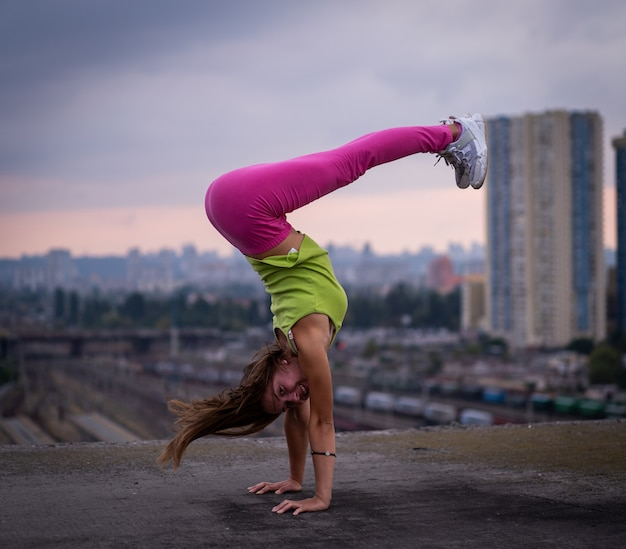 Flexible girl keep balance on hands on the cityscape background  concept of creativity and balance