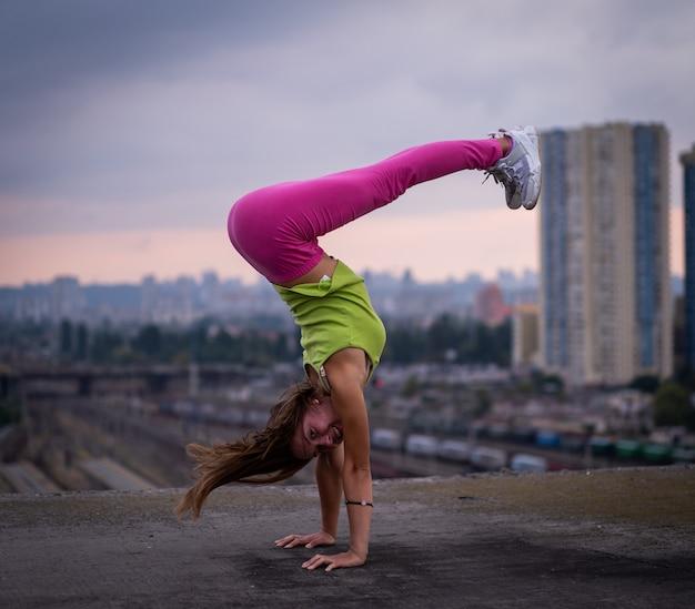 유연한 소녀는 도시 경관 배경의 창의성과 균형 개념에서 균형을 유지합니다.