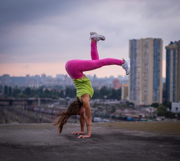유연한 소녀는 도시 경관 배경의 창의성 균형과 개성에 대한 균형을 유지합니다.