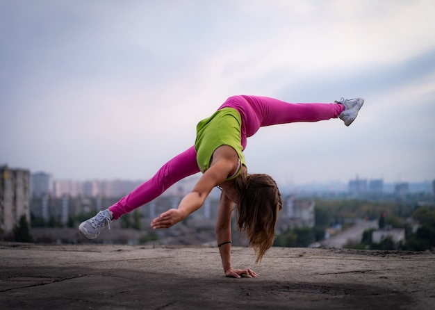유연한 소녀는 한 손으로 균형을 유지하여 도시 경관 배경의 잠재력 개념에 대해 분할합니다.