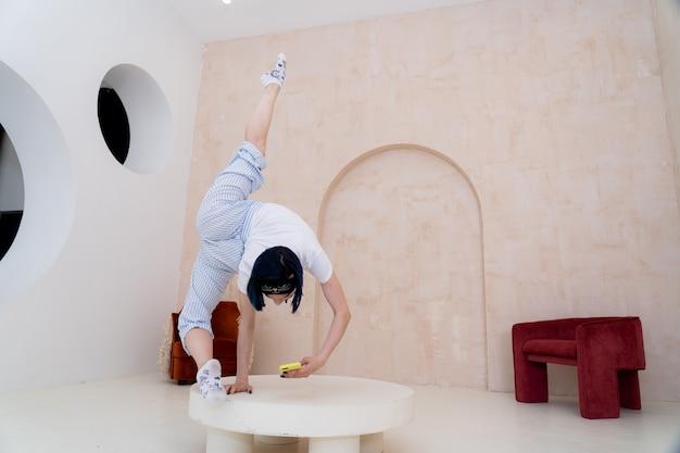 Гибкая девушка держит баланс на одной руке, пока смартфон дома концепция скуки во время самоизоляции covid