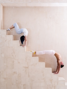 Flexible girl and man doing stretching and handstand in studio concept of individuality creativity and selfconfidence
