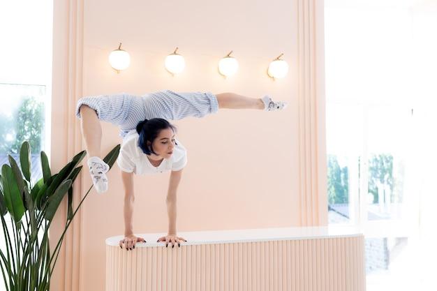 Гибкая девушка практикует растяжку и стойку на руках дома концепция карантинного времени во время самоизоляции ...