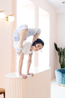 Flexible girl practice stretching and handstand at home concept of individuality creativity and self...