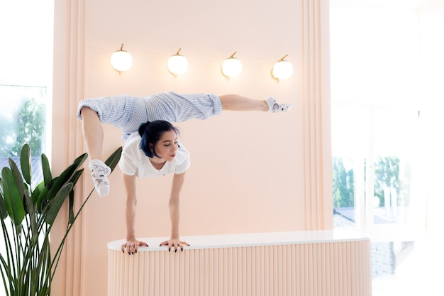 Flexible girl practice stretching and handstand at home concept of quarantine time during self isola...
