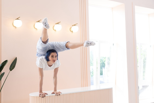 Flexible girl practice stretching and handstand at home concept of quarantine time during self isolation