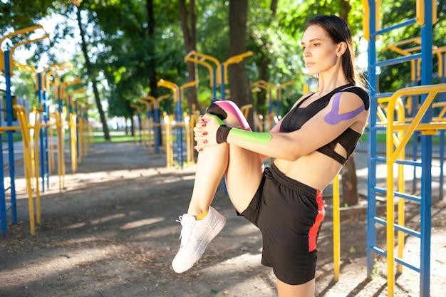 다리를 스트레칭, 검은 스포츠 복장을 입고 유연한 화려한 근육 여자. 젊은 자신감 갈색 머리 여자 선수 체조 연습, 워밍업, 몸에 다채로운 kinesiotaping.
