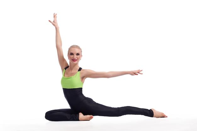 유연한 체조 선수. 그녀의 공연이 바닥에 고립 된 copyspace에 앉아 우아하게 포즈를 취하는 아름다운 여성 체조 선수의 가로 샷