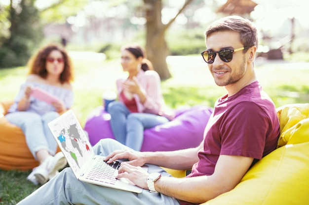 유연한 시간. 좋은 콘텐츠 남자가 의자에 앉아 자신의 노트북에서 작업 프리미엄 사진