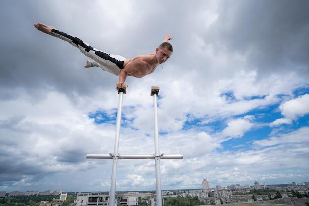 유연한 남성 서커스 아티스트는 놀라운 클라우드 스케이프에 대해 한 손으로 균형을 유지합니다.