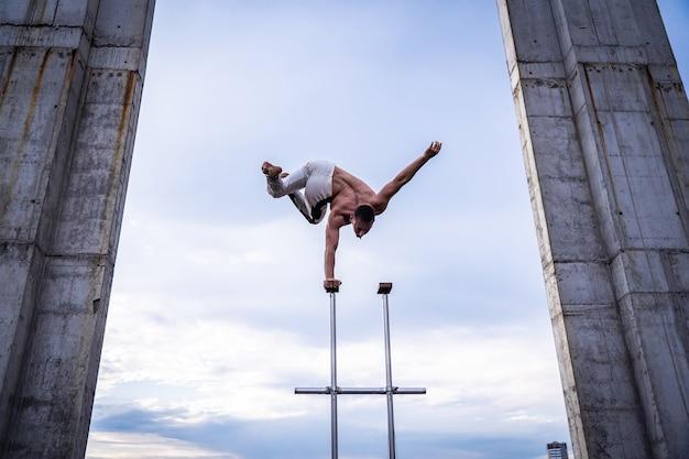 유연한 남성 서커스 아티스트는 콘크리트 구조에서 한 손으로 균형을 유지합니다.