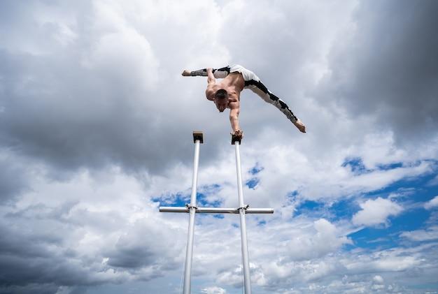 Гибкий цирковой артист мужского пола удерживает равновесие одной рукой на крыше на фоне удивительных облаков.