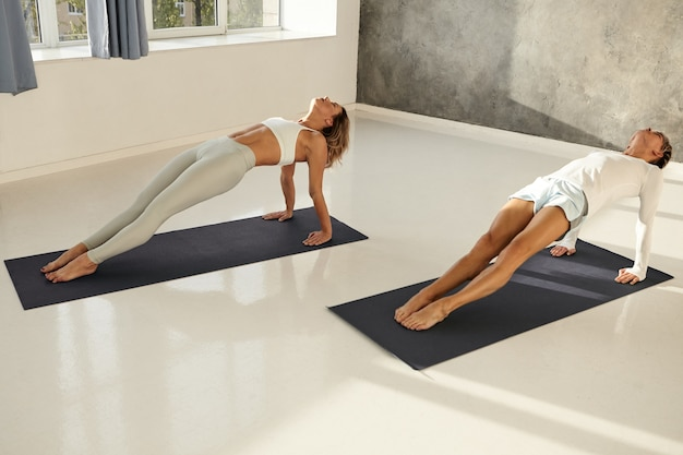 Flexible muscular athletes wearing sports clothes doing backwards plank on mats in gym. barefoot man and woman doing yoga asanas to strengthen arms and torso. fitness, endurance and determination