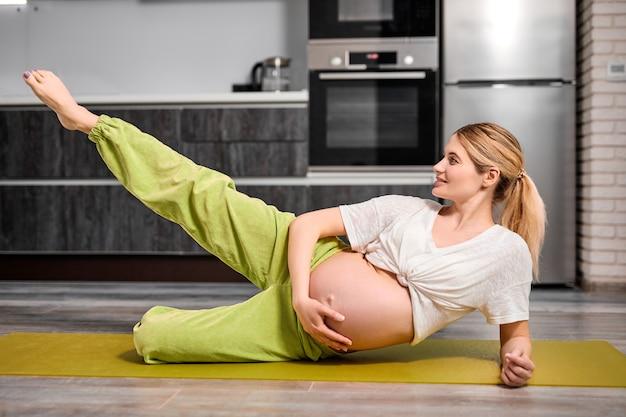 Гибкая беременная женщина с обнаженным животиком поднимает одну ногу вверх, делая упражнения на полу