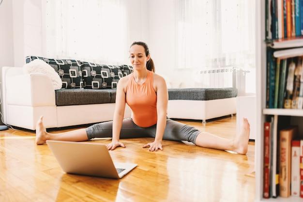 Гибкая беременная женщина-йог сидит на полу в позе йоги с разделенными ногами и следует онлайн-руководству.