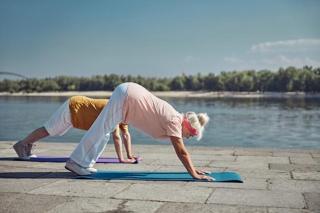 柔軟な年配の女性と下向きの犬の運動をしている男性