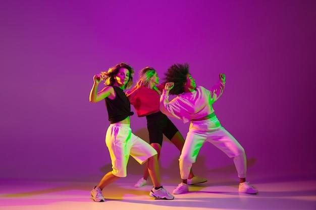 유연한. 녹색 네온 불빛으로 댄스 홀에서 보라색 분홍색 배경에 세련된 옷을 입고 힙합을 춤추는 낚시를 좋아하는 소녀들. 청소년 문화, 운동, 스타일 및 패션, 액션. 유행 초상화입니다.
