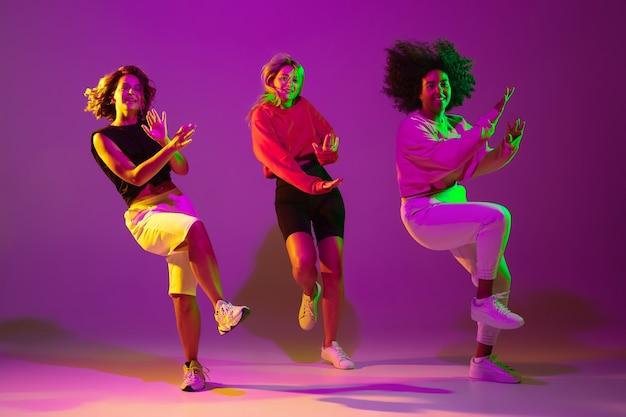 유연한. 녹색 네온 불빛으로 댄스 홀에서 보라색 분홍색 배경에 세련된 옷을 입고 힙합을 춤추는 낚시를 좋아하는 소녀들. 청소년 문화, 운동, 스타일과 패션, 액션. 유행 초상화입니다.