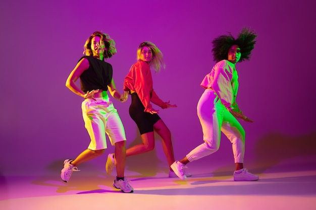 Flexible. sportive girls dancing hip-hop in stylish clothes on purple-pink background at dance hall in green neon light. youth culture, movement, style and fashion, action. fashionable portrait.