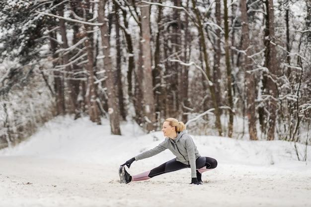 눈 덮인 겨울날 숲에서 스트레칭과 워밍업 운동을 하는 유연한 스포츠우먼. 건강한 라이프 스타일, 야외 피트니스