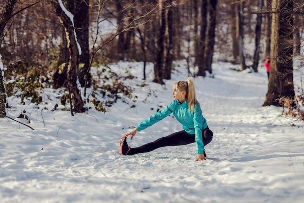 派手な冬の日に自然の中でウォームアップとストレッチ運動を行う柔軟なスポーツウーマン。健康的なライフスタイル、冬のフィットネス、柔軟性