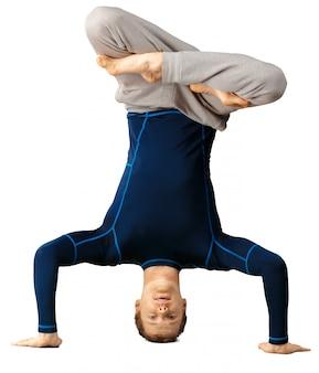 Гибкий спортивный молодой человек делает упражнения на растяжку на белом
