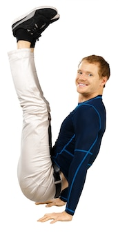 Flexible sporty young man doing stretching exercises isolated on white