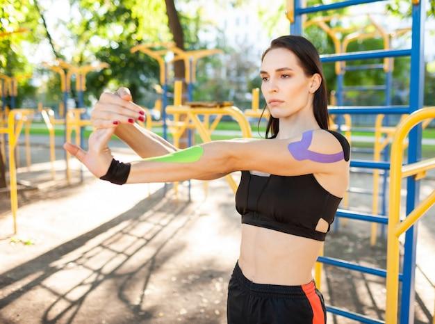 팔을 스트레칭 검은 스포츠 복장을 입고 유연한 멋진 근육 갈색 머리 여자. 체조 연습, 워밍업, 몸에 다채로운 kinesiotaping 젊은 자신감 여성 운동 선수.