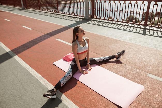 유연한 여성은 여름날 야외 매트에 앉아 스트레칭 운동을 한다