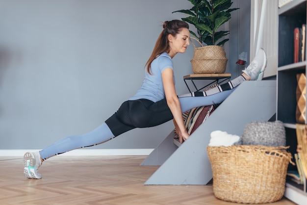 自宅でフロントスプリットストレッチ運動をしている柔軟な女性。