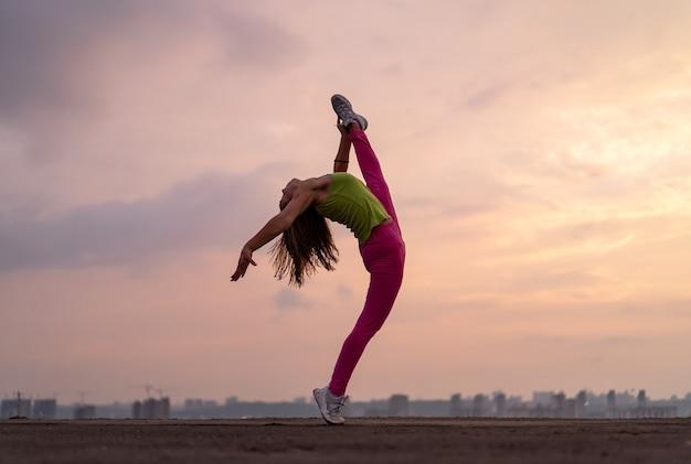 Гибкая женщина делает сплит на открытом воздухе на фоне драматического заката