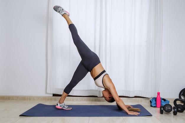 自宅でのトレーニング中にヨガの練習をしている柔軟な女性