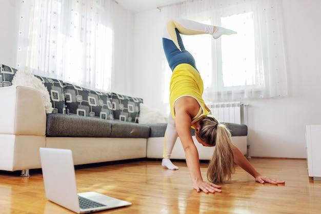 Flexible woman in downward-facing dog yoga pose at home.